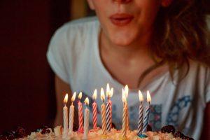 dziewczynka zdmuchuje tort urodzinowy